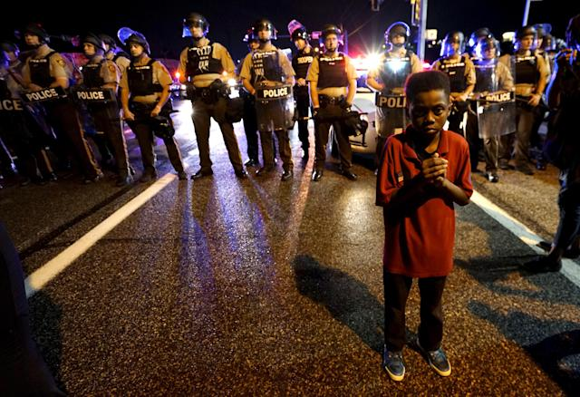 <p>Amarion Allen, 11-years-old, stands in front of a police line shortly before shots were fired in a police-officer involved shooting in Ferguson, Missouri August 9, 2015. Two people were shot in the midst of a late-night confrontation between riot police and protesters, after a day of peaceful events commemorating the fatal shooting of Michael Brown by a white officer one year ago. (Rick Wilking/Reuters) </p>