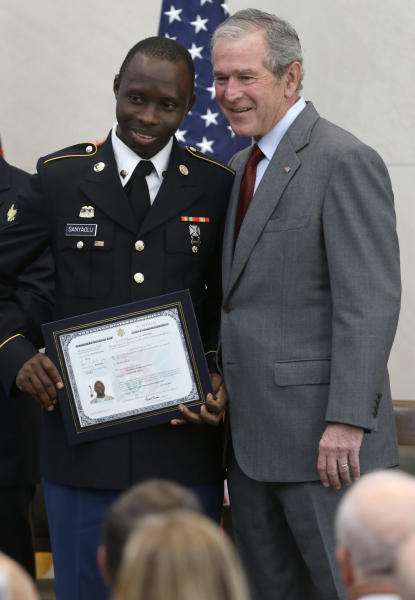 Former President George W. Bush, right, poses for a photo with Taofeek Adeyemi Sanyaolu, of Nigeria, with his U.S. citizen certificate after a ceremony at the The George W. Bush Presidential Center in Dallas, Wednesday, July 10, 2013. Twenty new citizens took the oath of U.S. citizenship at the former president's library. (AP Photo/LM Otero)
