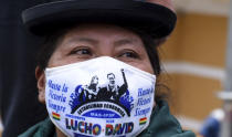 A woman wearing a mask amid the coronavirus pandemic with the image Bolivia's new President Luis Arce and Vice President David Choquehuanca stand at Plaza Murillo during their inauguration in La Paz, Bolivia, Sunday, Nov. 8, 2020. (AP Photo/Sara Aliaga)