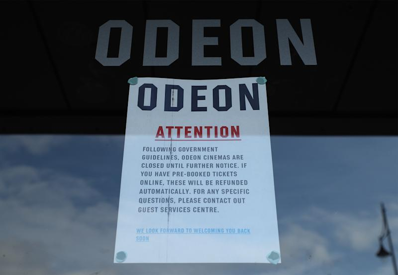 A sign in the door of an Odeon cinema in South Woodford, London, which has closed due to coronavirus. On Monday Prime Minister Boris Johnson called on people to stay away from pubs, clubs and theatres, work from home if possible and avoid all non-essential contacts and travel in order to reduce the impact of the coronavirus pandemic. (Photo by Yui Mok/PA Images via Getty Images)