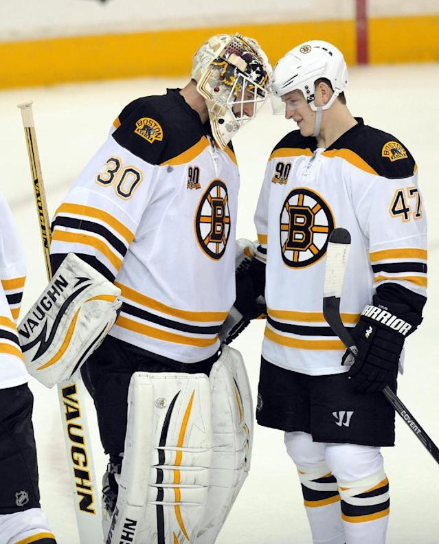 Boston Bruins goalie Chad Johnson (30) celebrates their 4-2 win over the Washington Capitals with Torey Krug (47) after an NHL hockey game, Saturday, March 29, 2014, in Washington. (AP Photo/Nick Wass)