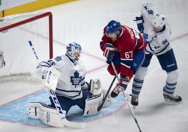 Montreal Canadiens' Max Pacioretty (67) jumps as he tries to deflect a shot past Toronto Maple Leafs goalie Jonathan Bernier with defenseman Dion Phaneuf (3) behind during the first period of an NHL hockey game Saturday, Nov. 30, 2013 in Montreal. (AP Photo/The Canadian Press, Paul Chiasson)