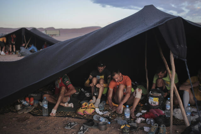 Competitors prepare in a bivouac before sunrise as they get ready to take part in the 33rd edition of Marathon des Sables, in the Sahara desert, near Merzouga, southern Morocco, Friday, April 13, 2018. Under a hot desert sun and with the desolation of the Sahara all around, about 1,000 competitors from 50 countries took part in this year's Marathon des Sables, or Marathon of the Sands. The 33rd edition of the annual race, considered to be one of the most demanding ultramarathons in the world, finished Saturday after six grueling days and about 250 kilometers (150 miles). (AP Photo/Mosa'ab Elshamy)