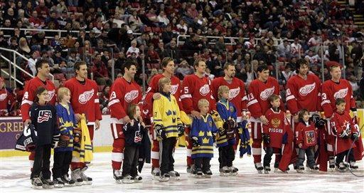 Olympic bound Detroit Red Wings stand with their children and teammates' children before the start of the hockey game against the Colorado Avalance in Detroit, Sunday, Feb. 12, 2006. From left are Chris Chelios and Tara Chelios representing the United States; Henrik Zetterberg and Michael Babcock representing Sweden; Mathieu Schneider and Matt Schneider representing the United States; Mikael Samuelsson and Kevin Lidstrom representing Sweden; Nicklas Lidstrom and Samuel Lidstrom representing Sweden; Tomas Holmstrom and Adam Lidstrom representing Sweden; Pavel Datsyuk and Igor Larionov representing Russia; Robert Lang and Kelly Lang representing the Czech Republic and Kris Draper and Jack Sanko representing Canada. (AP Photo/Carlos Osorio)