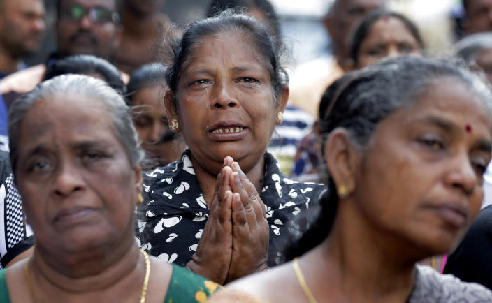 Sri Lankan Catholics pray on a road during a brief holly Mass held outside the exploded St. Anthony's Church marking the seventh day of the Easter Sunday attacks in Colombo, Sri Lanka, Sunday, April 28, 2019. Sri Lanka's Catholics on Sunday awoke to celebrate Mass in their homes by a televised broadcast as churches across the island nation shut over fears of militant attacks, a week after the Islamic State-claimed Easter suicide bombings. (AP Photo/Eranga Jayawardena)