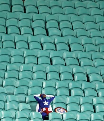 10ThingstoSeeSports - A lone U.S. supporter dressed as 'Captain America' sits in the stands after Belgium defeated the U.S. 2-1 in extra time to advance to the quarterfinals during the World Cup round of 16 soccer at the Arena Fonte Nova in Salvador, Brazil, Tuesday, July 1, 2014. (AP Photo/Natacha Pisarenko, File)