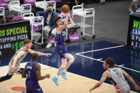 Charlotte Hornets guard LaMelo Ball (2) shoots against Washington Wizards forward Davis Bertans, left, and center Robin Lopez (15) during the first half of an NBA basketball game, Sunday, May 16, 2021, in Washington. Hornets center Bismack Biyombo, second from left. looks on. (AP Photo/Nick Wass)