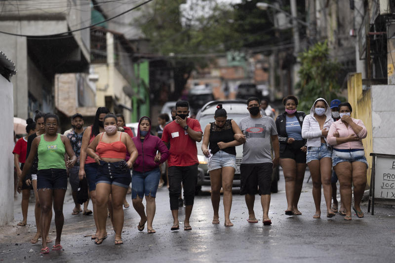 Residents, some wearing masks as a precaution against the spread of the new coronavirus, walk together as they accompany a car transporting the remains of several people who died in an armed confrontation in the Alemao slums complex in Rio de Janeiro, Brazil, Friday, May 15, 2020. According to the civil police, 10 people were found dead during the police operation against alleged drug traffickers. (AP Photo/Leo Correa)