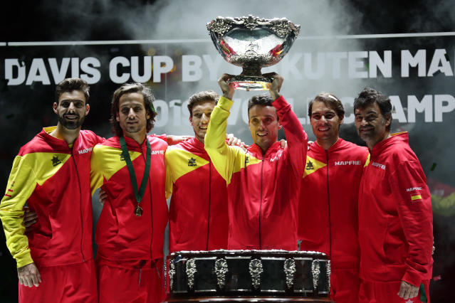 Spain's Roberto Bautista Agut lifts the trophy as the Spanish team poses after Spain defeated Canada 2-0 to win the Davis Cup final in Madrid, Spain, Sunday, Nov. 24, 2019. (AP Photo/Manu Fernandez)