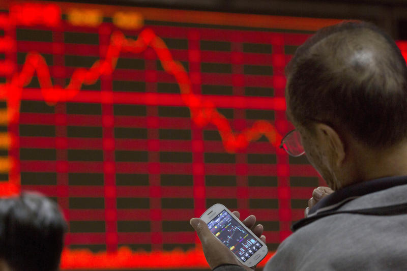 FILE - In this Tuesday, July 14, 2015, file photo, an investor looks at his smart phone displaying stock prices at a brokerage in Beijing. Beijing's failed efforts to avert a crash in its stock market raised the possibility it might not succeed in letting the air out of a massive credit and property bubble without tripping up the world's second biggest economy and sending markets elsewhere crashing. (AP Photo/Ng Han Guan)