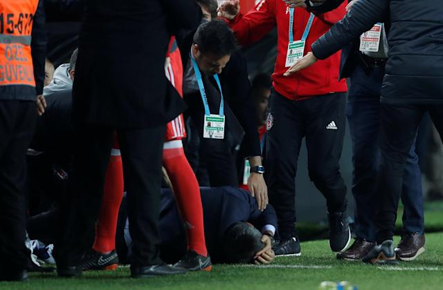 Soccer Football - Turkish Cup - Semi Final - Fenerbahce vs Besiktas - Sukru Saracoglu Stadium, Istanbul, Turkey - April 19, 2018 Besiktas coach Senol Gunes is on the floor after being hit by an object REUTERS/Murad Sezer