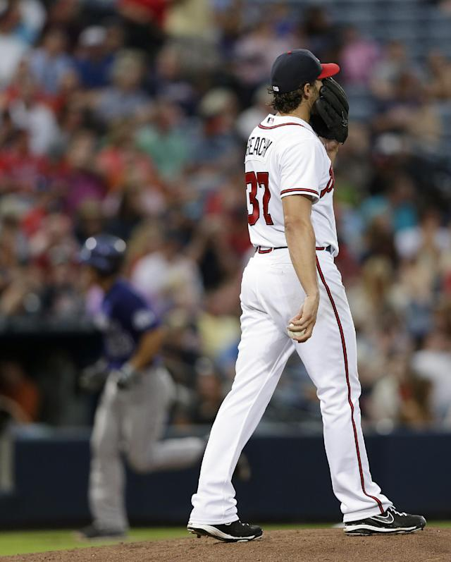 Atlanta Braves starting pitcher Brandon Beachy (37) paces on the mound as Colorado Rockies' Nolan Arenado (28) rounds the bases after hitting a home run in the fourth inning of a baseball game in Atlanta, Monday, July 29, 2013. (AP Photo/John Bazemore)