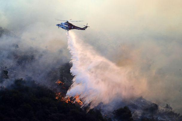 PHOTO: A helicopter drops water as the Getty fire burns on Mandeville Canyon, Oct. 28, 2019, in Los Angeles. (Marcio Jose Sanchez/AP)