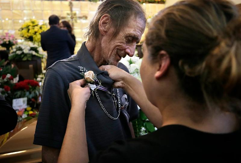 An El Pasoan pins a flower to the shirt of Antonio Basco at a prayer service Friday, Aug. 16, 2019, for his wife Margie Reckard at La Paz Faith Center in El Paso, Texas. His wife was one of the 22 people killed in the Walmart mass shooting on Aug. 3, 2019.