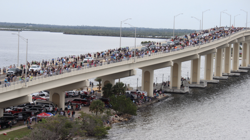 Pictured is a large crowd of people on the Max Brewer Bridge gathering to watch the SpaceX launch.