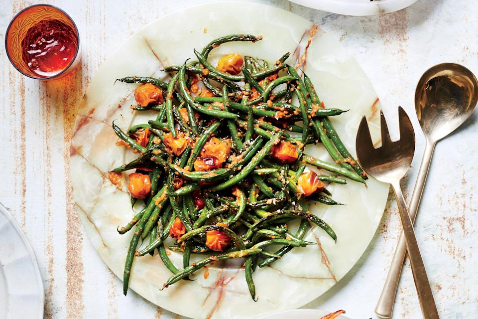 "Inspired by Spanish romesco, this easy side dish involves cherry tomatoes roasted until they're sweet and rich and just a little charred; blended into a sauce with garlic and almonds, they're just the thing the green beans need. <a href=""https://www.epicurious.com/recipes/food/views/blistered-green-beans-with-tomato-almond-pesto?mbid=synd_yahoo_rss"" rel=""nofollow noopener"" target=""_blank"" data-ylk=""slk:See recipe."" class=""link rapid-noclick-resp"">See recipe.</a>"