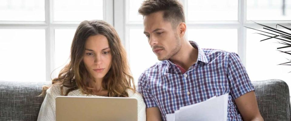 Couple sitting on a couch looking at papers and laptop, looking concerned