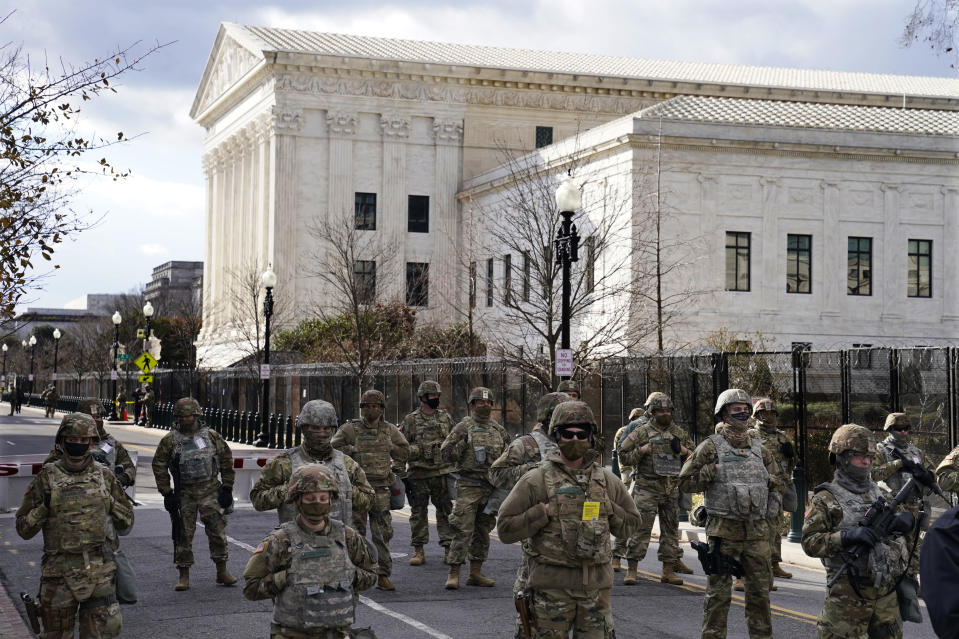 FILE - In this Wednesday, Jan. 20, 2021 file photo, members of the National Guard stand at a road block near the Supreme Court ahead of President-elect Joe Biden's inauguration ceremony in Washington. On Friday, Jan. 29, 2021, The Associated Press reported on stories circulating online incorrectly asserting Donald Trump invited National Guard members to stay at Trump Hotel in Washington so they don't have to sleep in a cold parking garage. A spokesperson with the National Guard Bureau told The Associated Press they had not received any offers to stay at Trump International Hotel Washington, D.C., the former president's hotel. (AP Photo/John Minchillo)