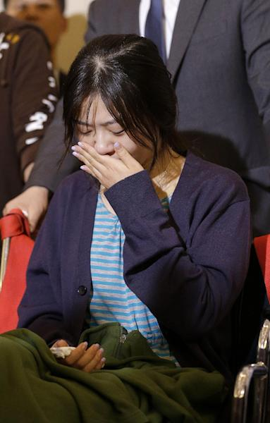 An unidentified flight attendant of Asiana Flight 214, which crashed on Saturday, July 6, 2013, cries during a news conference at San Francisco International Airport in San Francisco, Wednesday, July 10, 2013. Two passengers were killed and many others were injured in the crash. (AP Photo/Jeff Chiu)