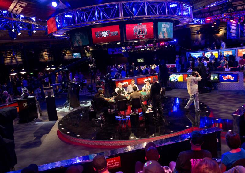 Eight of 25 remaining players engage in a round of Texas Hold 'em at the feature table during the World Series of Poker, Monday, July 15, 2013, in Las Vegas. More than a dozen eliminations stand between the remaining players in the world series main event and a ticket for a November finale worth $8.4 million to the winner. (AP Photo/Julie Jacobson)