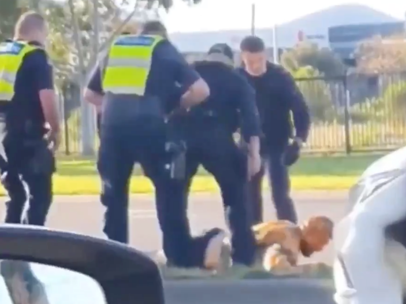 Victoria Police officers surround a man on the ground after hitting him with a police car (7News)