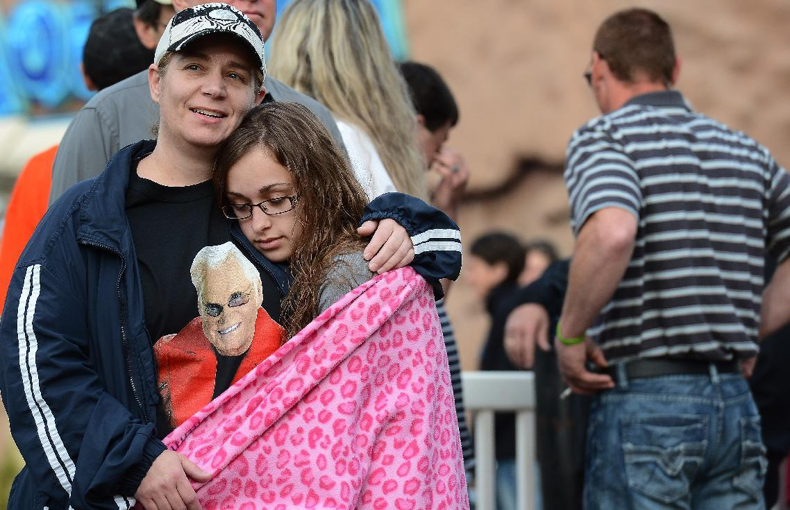 Terah Jones, left, comforts her daughter Katie, of Burleson Texas, while waiting to enter the Grand Ole Opry House for the funeral of country music star George Jones on Thursday, May 2, 2013, in Nashville, Tenn. Jones, a country music legend who had No. 1 hits in four separate decades, died April 26. (AP Photo/Mark Zaleski)