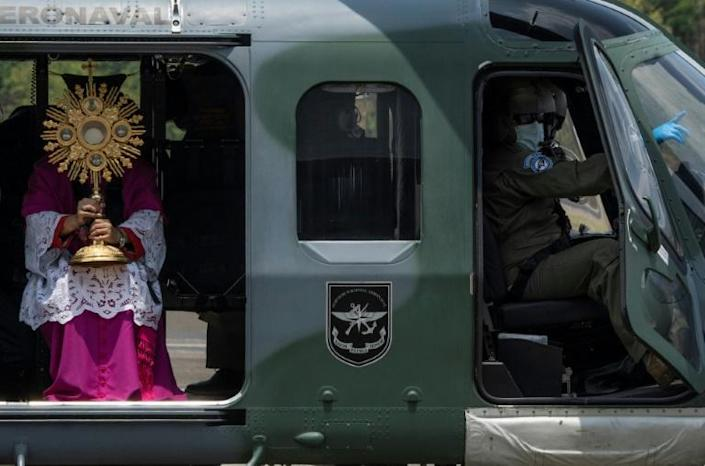 Panama's Archbishop Jose Domingo Ulloa holds the Blessed Sacrament as he sits in a helicopter at Howard Air Force Base in Panama City before overflying the capital on April 5, 2020 (AFP Photo/Luis ACOSTA)