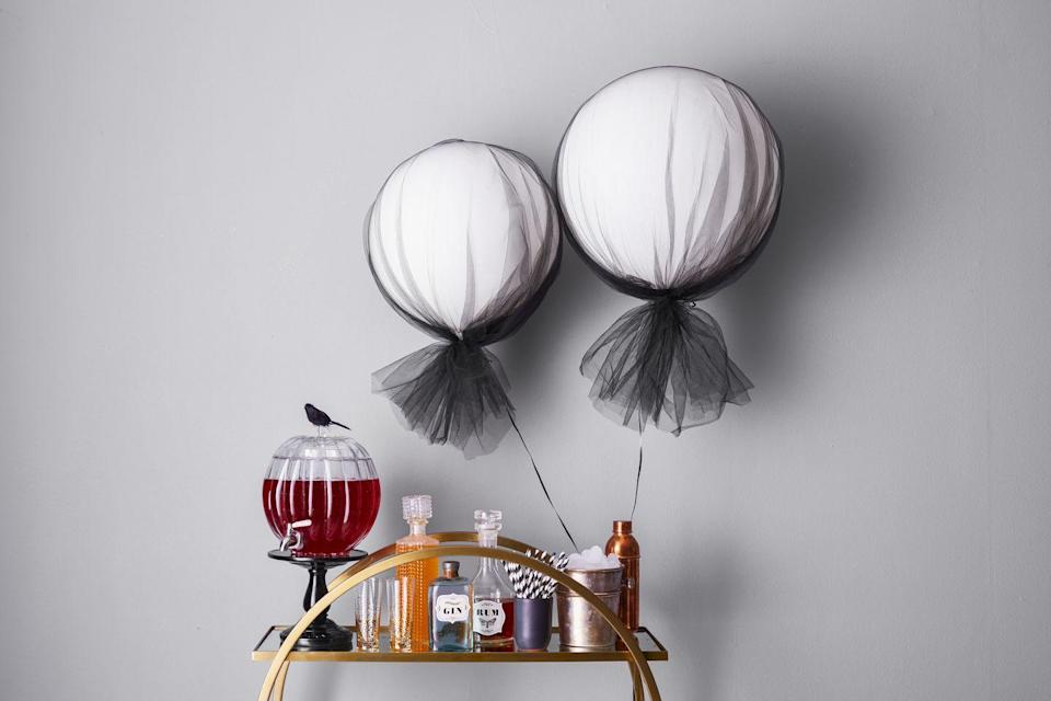 """<p>Encourage guests to help themselves by sticking <a href=""""https://www.goodhousekeeping.com/holidays/halloween-ideas/a46024/halloween-labels/"""" rel=""""nofollow noopener"""" target=""""_blank"""" data-ylk=""""slk:spooky labels"""" class=""""link rapid-noclick-resp"""">spooky labels</a> to clear decanters. Oversized helium <a href=""""https://www.amazon.com/12-Latex-White-Balloons-72ct/dp/B0016KVWEQ?tag=syn-yahoo-20&ascsubtag=%5Bartid%7C10055.g.565%5Bsrc%7Cyahoo-us"""" rel=""""nofollow noopener"""" target=""""_blank"""" data-ylk=""""slk:balloons"""" class=""""link rapid-noclick-resp"""">balloons</a> wrapped with <a href=""""https://www.amazon.com/54-Tulle-Fabric-Bolt-40yds-Black/dp/B014II88TO/?tag=syn-yahoo-20&ascsubtag=%5Bartid%7C10055.g.565%5Bsrc%7Cyahoo-us"""" rel=""""nofollow noopener"""" target=""""_blank"""" data-ylk=""""slk:tulle"""" class=""""link rapid-noclick-resp"""">tulle</a> signal where the <em>real </em>party's at.  </p>"""