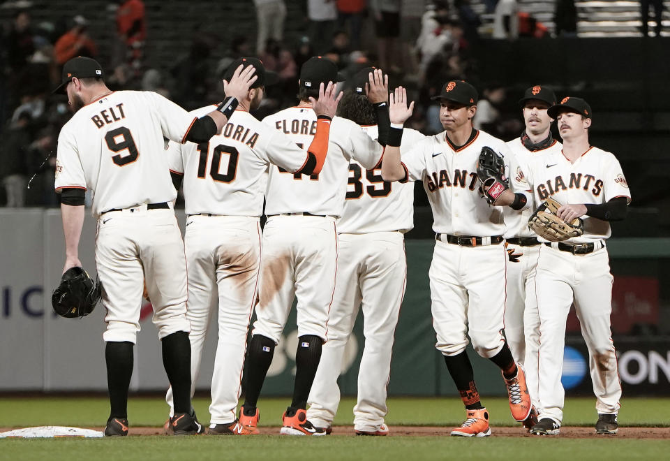 SAN FRANCISCO, CALIFORNIA - MAY 10: Mauricio Dubon #1 of the San Francisco Giants front, right, and his teammates celebrate defeating the Texas Rangers 3-1 at Oracle Park on May 10, 2021 in San Francisco, California. (Photo by Thearon W. Henderson/Getty Images)