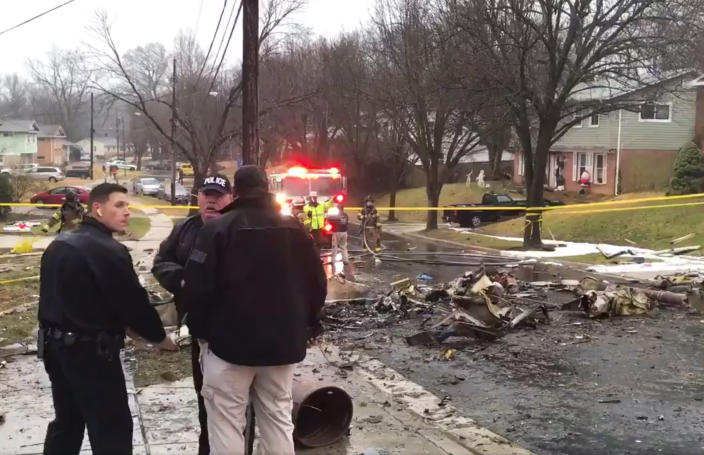 In this image made from video provided by the Prince George's County Fire and Emergency Medical Services Department, firefighters and police officers investigate the scene of a small plane crash in the Lanham neighborhood, Md., Sunday, Dec. 29, 2019. The small plane crashed in the Maryland suburbs of the nation's capital Sunday, hitting a home's carport and killing at least a person aboard the aircraft, authorities said. (Prince George's County Fire/EMS via AP)