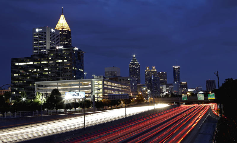 FILE - In this July 9, 2012 file photograph made using a long exposure, traffic moves along Interstate 75 against the downtown skyline in Atlanta. We're heavier in pounds and hotter by degrees than Americans of old. We're starting to snub our noses at distant suburbs after generations of burbs in our blood. Our roads and bridges are kind of a mess. There are many more poor, and that's almost sure to get worse. The average commuter wasted 14 hours stuck in traffic in 1982, 39 hours in 2005 and 34 hours in 2010, says the Texas Transportation Institute. (AP Photo/David Goldman, File)