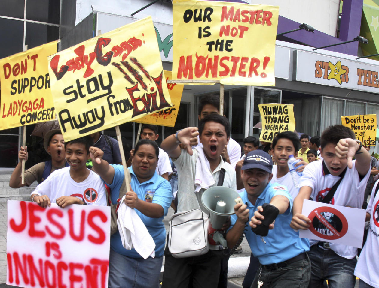 """Members of a religious group give thumbs-down signs as they shout """"Stop Lady Gaga Concert"""" during a rally near the venue of the pop diva's upcoming concert Saturday, May 19, 2012 in suburban Pasay, south of Manila, Philippines. They said they were offended by her music and videos, in particular her song """"Judas,"""" which they say mocks Jesus Christ. (AP Photo/Pat Roque)"""