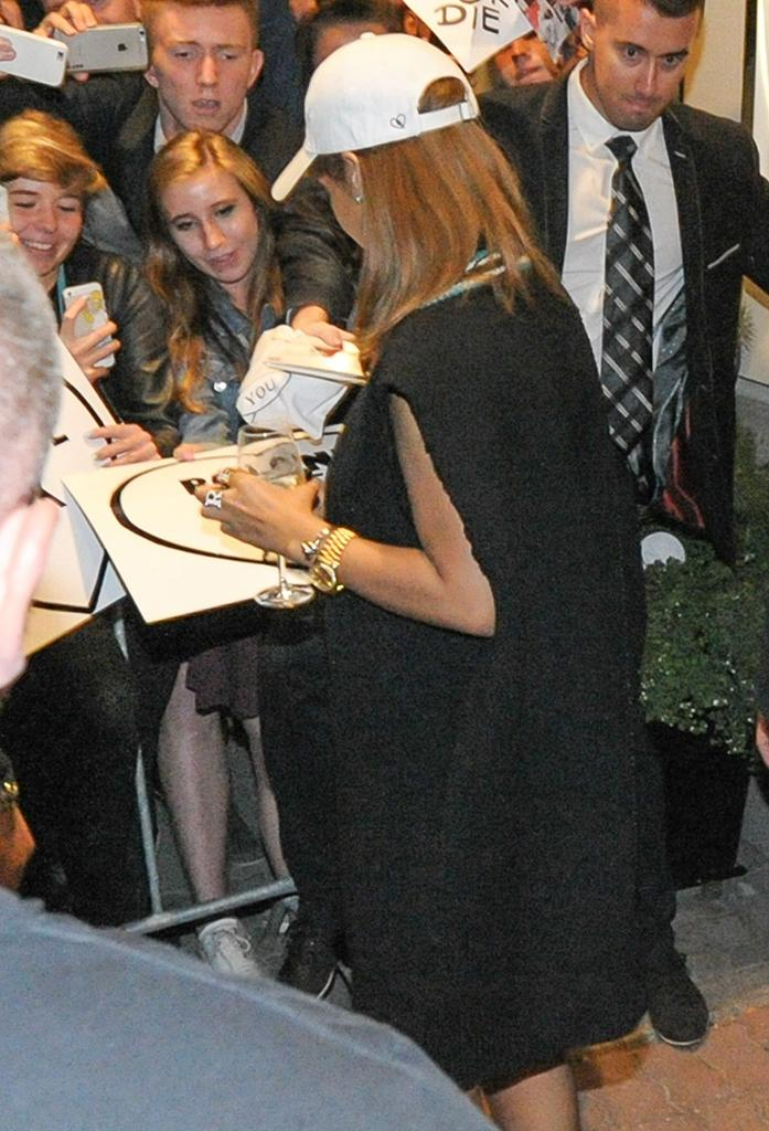 Rihanna signed autographs in Poland while holding a glass. (Photo: FameFlynet)