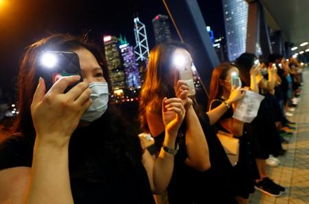 Protesters light up their smartphones as they form a human chain during a rally to call for political reforms in Hong Kong's Central district