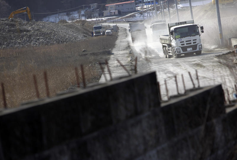 In this Tuesday, March 4, 2014 photo, dumpsters kick up clouds of dirt as they head to construction sites in Otsuchi, Iwate Prefecture, northeastern Japan. Construction has only begun at two of 10 planned sites in Otsuchi and further down the coast. (AP Photo/Junji Kurokawa)