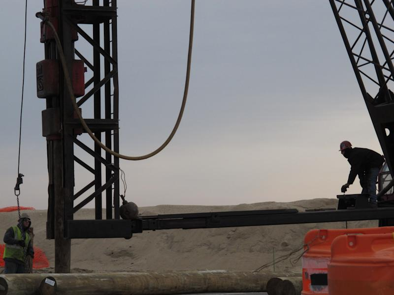 The operator of a pile driving machine, right, pulls a lever to begin raising a support plank for the new Belmar N.J. boardwalk on Monday, Jan. 21, 2013. Belmar is one of several shore towns that are adding steel sea walls  as an added layer of protection for the boardwalk as they rebuild walkways damaged by Superstorm Sandy. (AP Photo/Wayne Parry)
