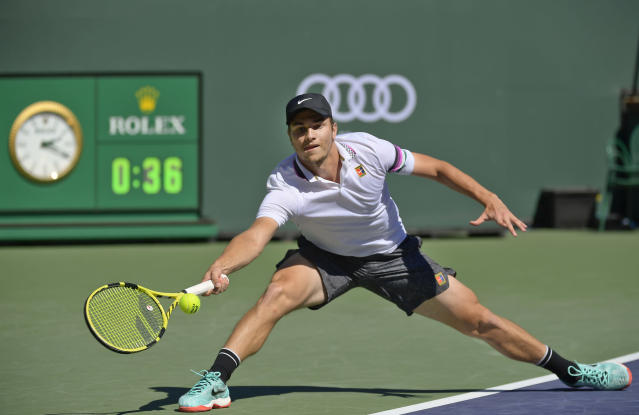 Miomir Kecmanovic, of Serbia returns a shot to Milos Raonic, of Canada at the BNP Paribas Open tennis tournament, Thursday, March 14, 2019, in Indian Wells, Calif. (AP Photo/Mark J. Terrill)