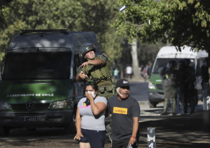 A Chilean policeman throws a tear gas canister toward anti-government demonstrators during a protest in Santiago, Chile, Friday, Dec. 27, 2019. Chile has been roiled by continuing and sometimes violent street protests since Oct. 18, when a student protest over a modest increase in subway fares turned into a much larger and broader movement with a long list of demands that largely focus on inequality. (AP Photo/Fernando Llano)