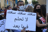 """An anti-government protester holds an Arabic placard that reads: """"Saad don't dream on it any more,"""" during a protest to denouncing the naming of former Prime minister Saad Hariri as a potential candidate as the country's new prime minister, in downtown Beirut, Lebanon, Wednesday, Oct. 21, 2020. Hariri resigned a year ago amid nationwide protests against government corruption and mismanagement of Lebanon's resources. (AP Photo/Hussein Malla)"""