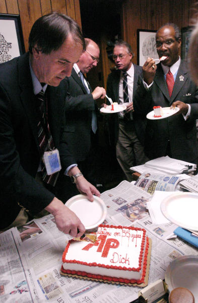 In a Monday Feb. 2, 2004 photo, Associated Press staff writer Dick Pettys, left, cuts a cake given to him in appreciation of his service to AP covering the state house, as House leaders eat in the background, after the general session at the Capitol in Atlanta. Pettys, a longtime political reporter for The Associated Press who was a fixture at the Georgia state Capitol for more than three decades and a well-respected mentor to other journalists, died Monday, Oct. 8, 2012 following a massive heart attack Monday afternoon at his north Georgia home. He was 66. (AP Photo/John Amis)
