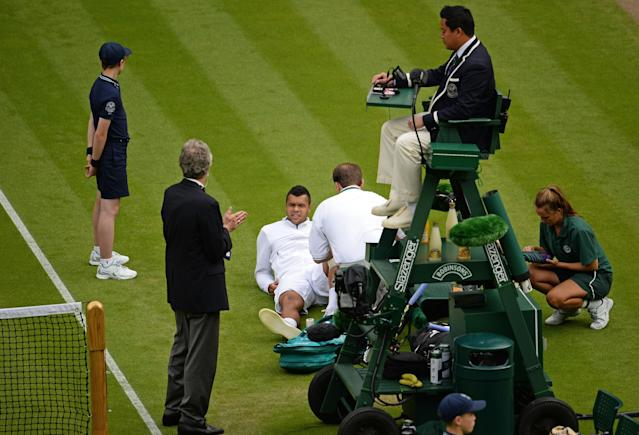 LONDON, ENGLAND - JUNE 26: Jo-Wilfried Tsonga of France receives treatment on court during his Gentlemen's Singles second round match against Ernests Gulbis of Latvia on day three of the Wimbledon Lawn Tennis Championships at the All England Lawn Tennis and Croquet Club on June 26, 2013 in London, England. (Photo by Mike Hewitt/Getty Images)