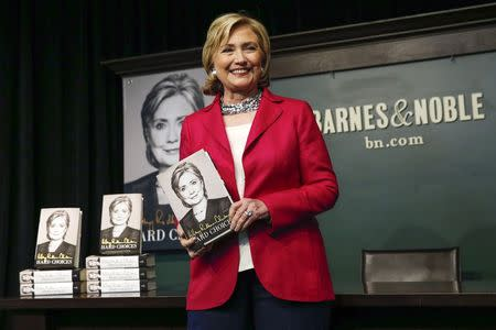 "Hillary Clinton poses with her new book ""Hard Choices"" during a book signing in New York"