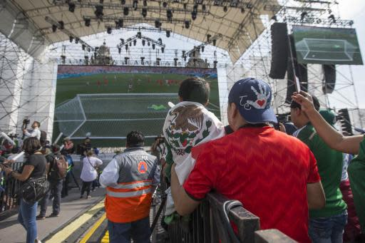 Mexico fans watch a live telecast of the Mexico vs. Korea World Cup soccer match in Mexico City's Zocalo, Sunday, June 23, 2018. (AP Photo/Christian Palma)