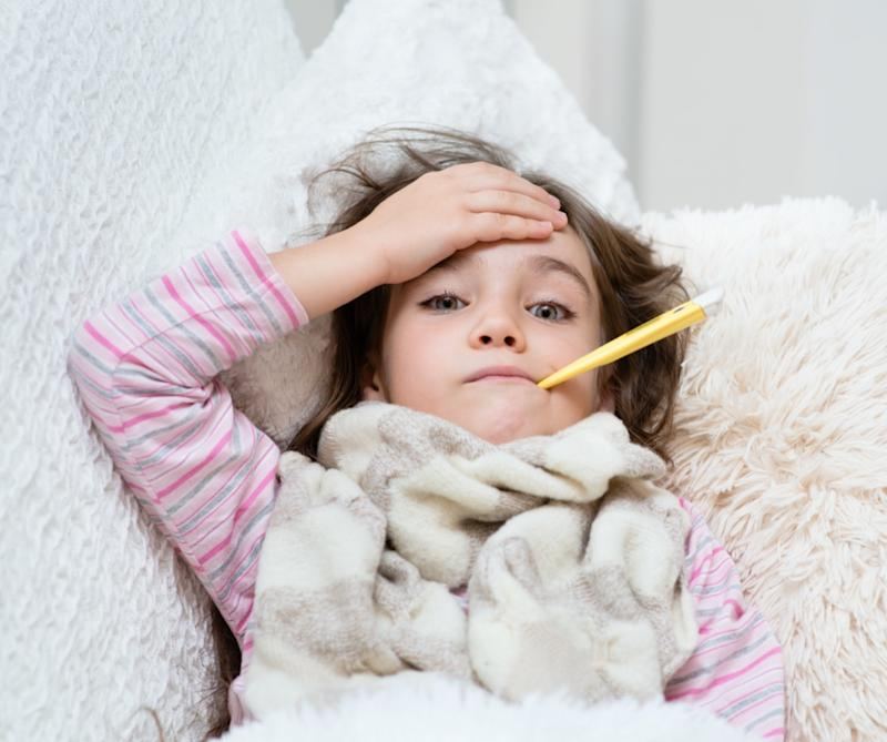 sick girl lying in bed with a thermometer in mouth and touch his forehead