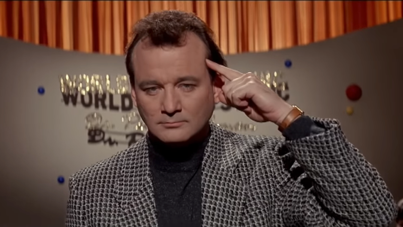 Bill Murray feigns telepathy by holding a finger to his temple in a scene from Ghostbusters II