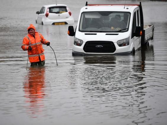 A worker recovers stranded vehicles from flood water on the A761 in Paisley, Scotland (Getty Images)