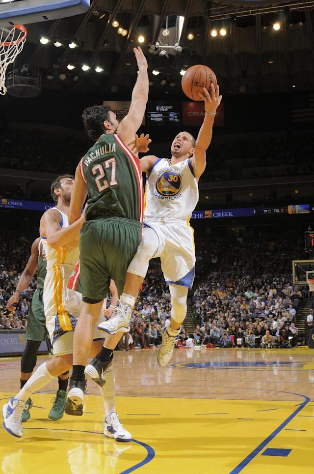 OAKLAND, CA - MARCH 20: Stephen Curry #30 of the Golden State Warriors shoots against Zaza Pachulia #27 of the Milwaukee Bucks on March 20, 2014 at Oracle Arena in Oakland, California. (Photo by Rocky Widner/NBAE via Getty Images)