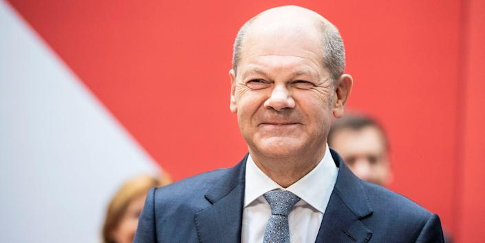 Olaf Scholz, wearing a suit and carrying a bouquet of flowers smiles after his party, the SPD, gathered the most votes in Germany's preliminary elections  results
