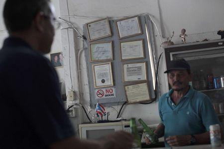 Roberto Torres (R) attends to a client next to government-issued licences and permits at his bar in San Juan, Puerto Rico, November 4, 2016. REUTERS/Alvin Baez