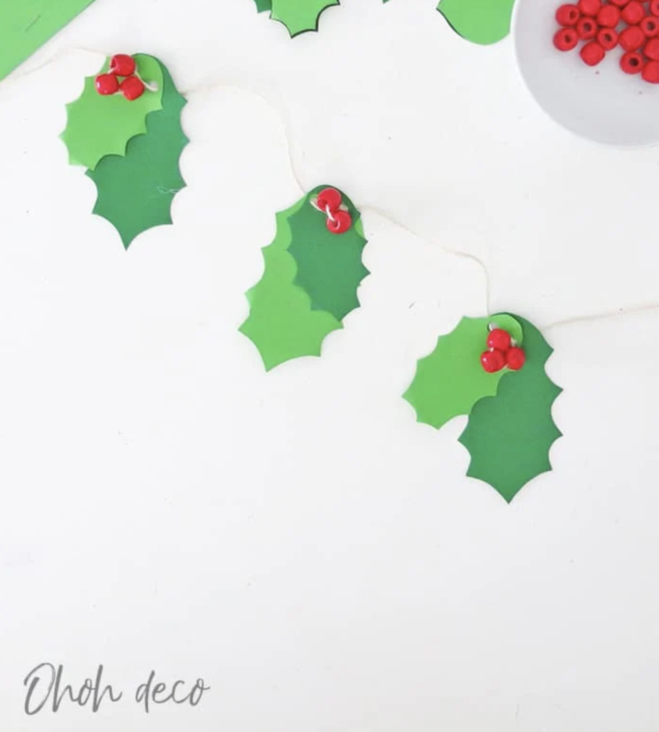 """<p>To make quick work of this Christmas garland, print the free design onto green cardstock and cut along the lines. Once that's done, all you'll have do is string the shapes onto twine with some red beads. </p><p><a href=""""https://www.ohohdeco.com/holly-christmas-garland-diy/"""" rel=""""nofollow noopener"""" target=""""_blank"""" data-ylk=""""slk:Get the tutorial."""" class=""""link rapid-noclick-resp"""">Get the tutorial.</a></p><p><a class=""""link rapid-noclick-resp"""" href=""""https://www.amazon.com/Assorted-Color-Design-Pieces-Plastic/dp/B07JKQ47WS?tag=syn-yahoo-20&ascsubtag=%5Bartid%7C10072.g.37499128%5Bsrc%7Cyahoo-us"""" rel=""""nofollow noopener"""" target=""""_blank"""" data-ylk=""""slk:SHOP BEADS"""">SHOP BEADS</a></p>"""